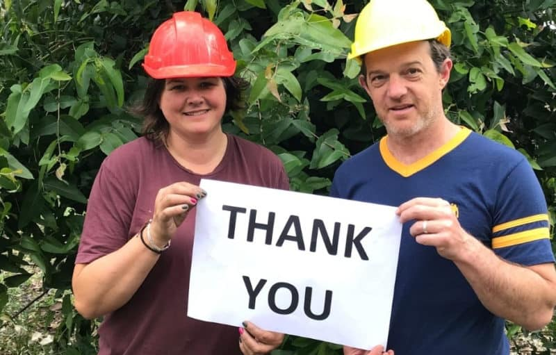 Sera and Kade, wearing hard hats, holding a THANK YOU sign